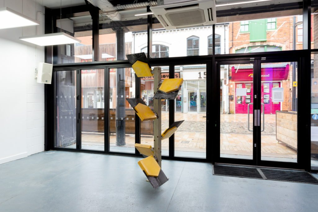 WayPoint, a sculpture by Leo Fitzmaurice in Gallery Café. The structure is made of six yellow and black Pay Point Company signs with logos removed.
